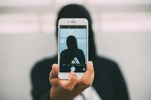 Pessoa branca, vestindo moletom e máscara preta, tirando uma selfie com a câmera traseira do celular.