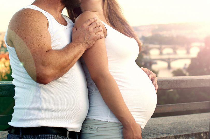 Mulher grávida e homem abraçados, ambos vestidos com camisetas brancas.