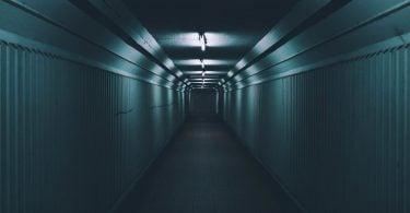 Corredor cinza vazio, com poucas luzes e muita sombra.
