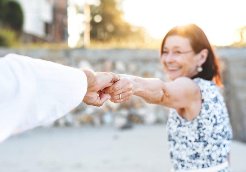 Idosa branca, com os cabelos morenos, sorrindo e dançando com idoso, em um parque ensolarado.