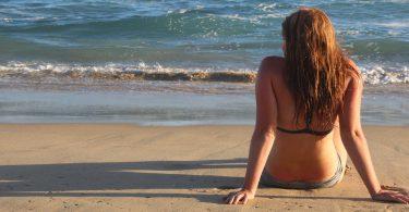 Menina branca, usando biquíni, setada na areia olhando para o mar.