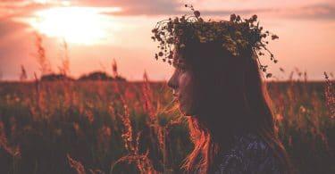 Menina branca, usando uma coroa de flores, no meio de um campo de flores, com um pôr do sol ao fundo.