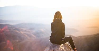 Mulher sentada em topo de montanha, observando o pôr do sol.