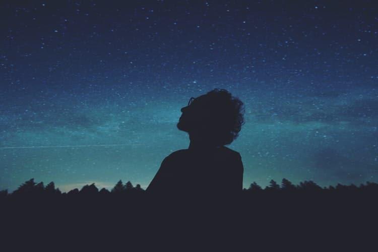 Silhueta de um homem olhando para o céu e ao fundo há um céu estrelado.