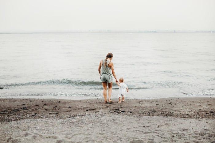 Mulher branca caminhando na areia, em direção ao mar, segurando a mão de criança pequena.