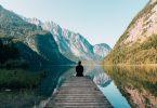 Homem vestido de preto, sentado em pier, observando lago, montanhas e céu azul.