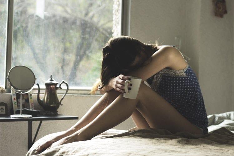 Mulher de pijama de bolinhas sentada em uma cama, com a cabeça nas pernas.