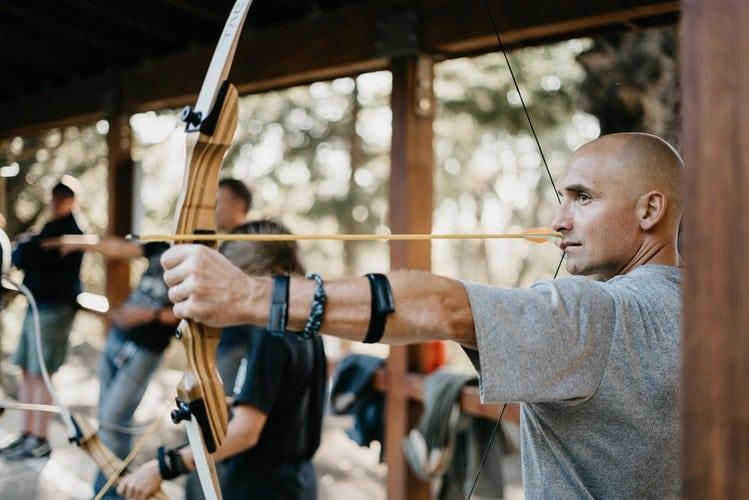 Homem careca segurando um arco e flecha.