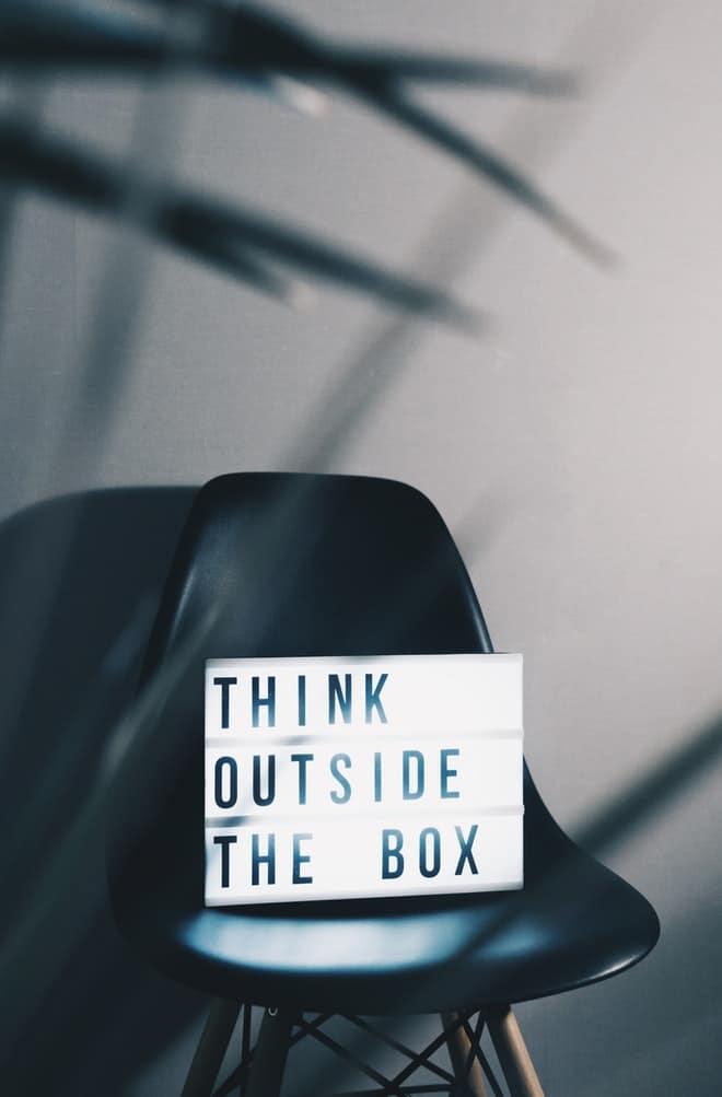 Cadeira preta encostada em parede cinza, com luminária acesa em cima da cadeira, escrito pense fora da caixa.