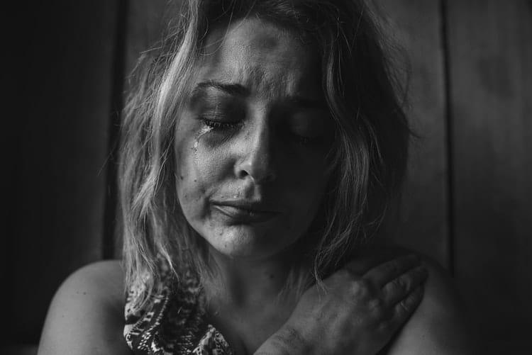 Foto preta e branca de mulher branca toda machucada, encolhida no chão, chorando.