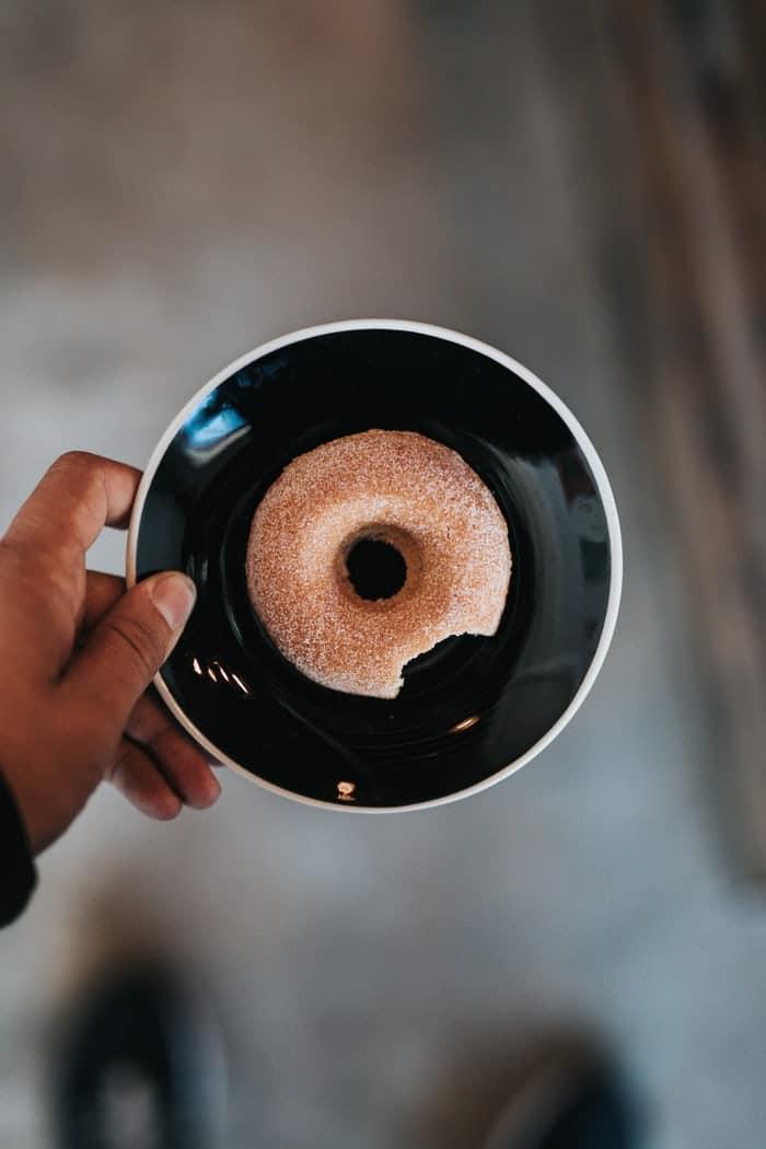 Mão de homem negro segurando um prato preto pequeno, com uma rosquinha açucarada mordida.