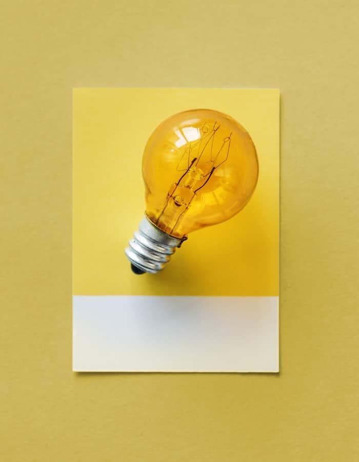 Foto de lampada laranja com fundo amarelo pendurada em parede amarela.