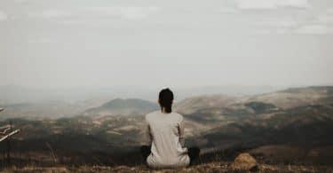 Mulher sentada na beira de uma montanha , em posição de meditação, observando o horizonte.