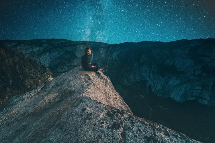 Moço sentado nas montanhas e ao fundo há um céu noturno estrelado.