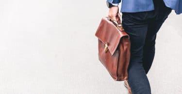 Homem vestido de terno, segurando pasta de couro marrom, caminhando.