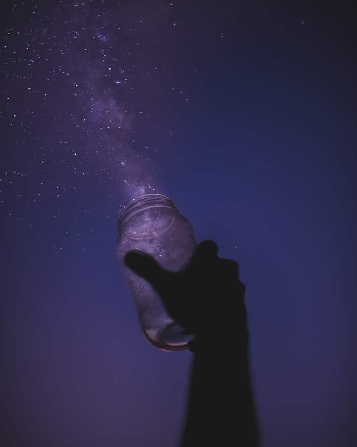 Mão de homem branco segurando pote de vidro para cima, apontando para o céu noturno estrelado.