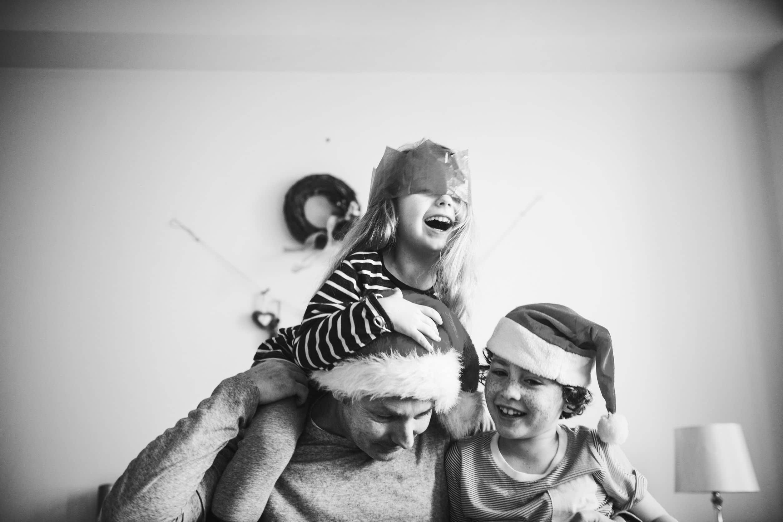Foto preta e branco de um homem vestindo uma toca de natal brincando com sua filha e seu filho.