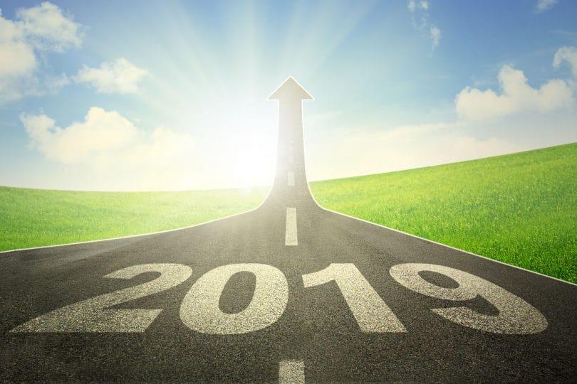 Imagem de estrada com número 2019 escrito no chão. Seta no final da estrada apontado para cima. Ao fundo o sol brilhando.