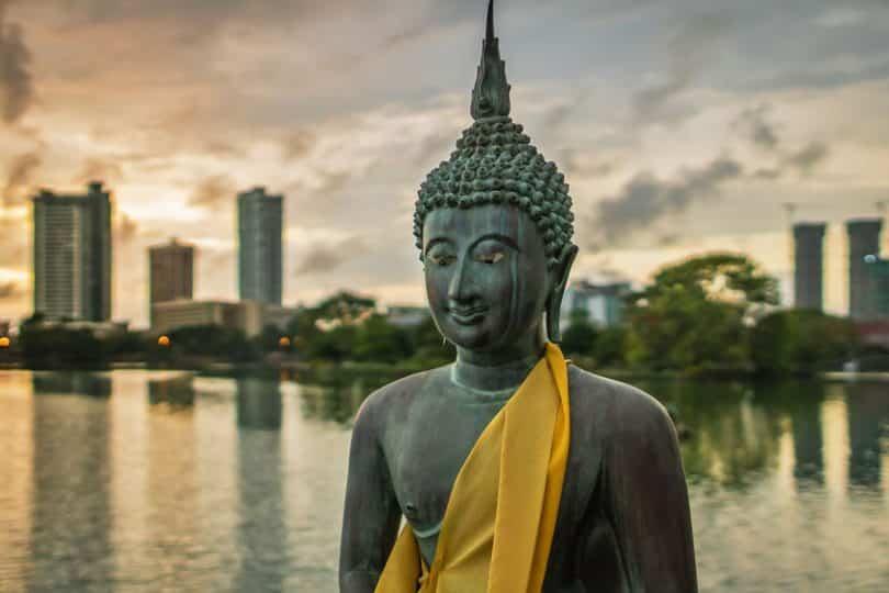 Estátua de Buda com lago e prédios ao fundo