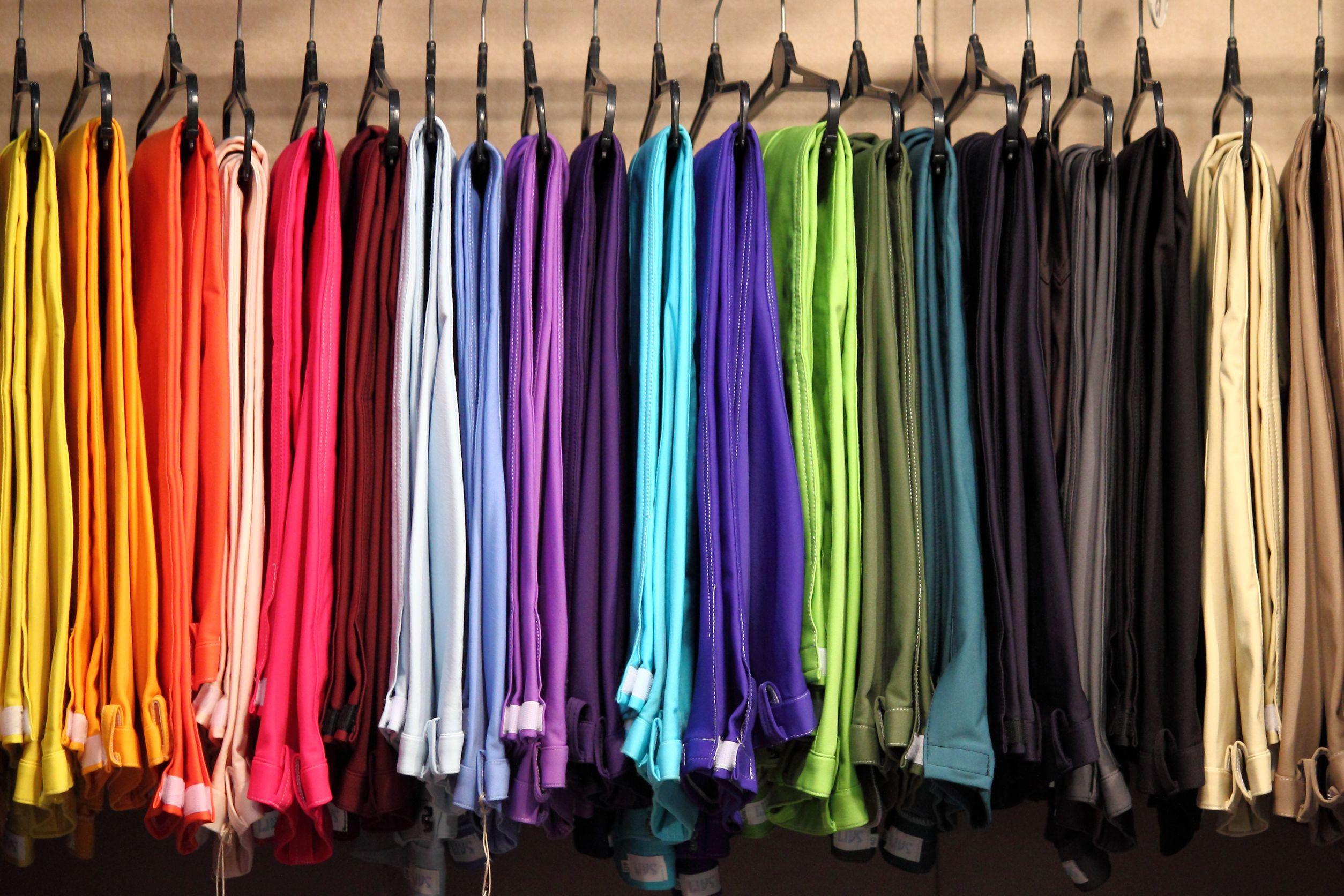 Lenços coloridos pendurados em cabides.
