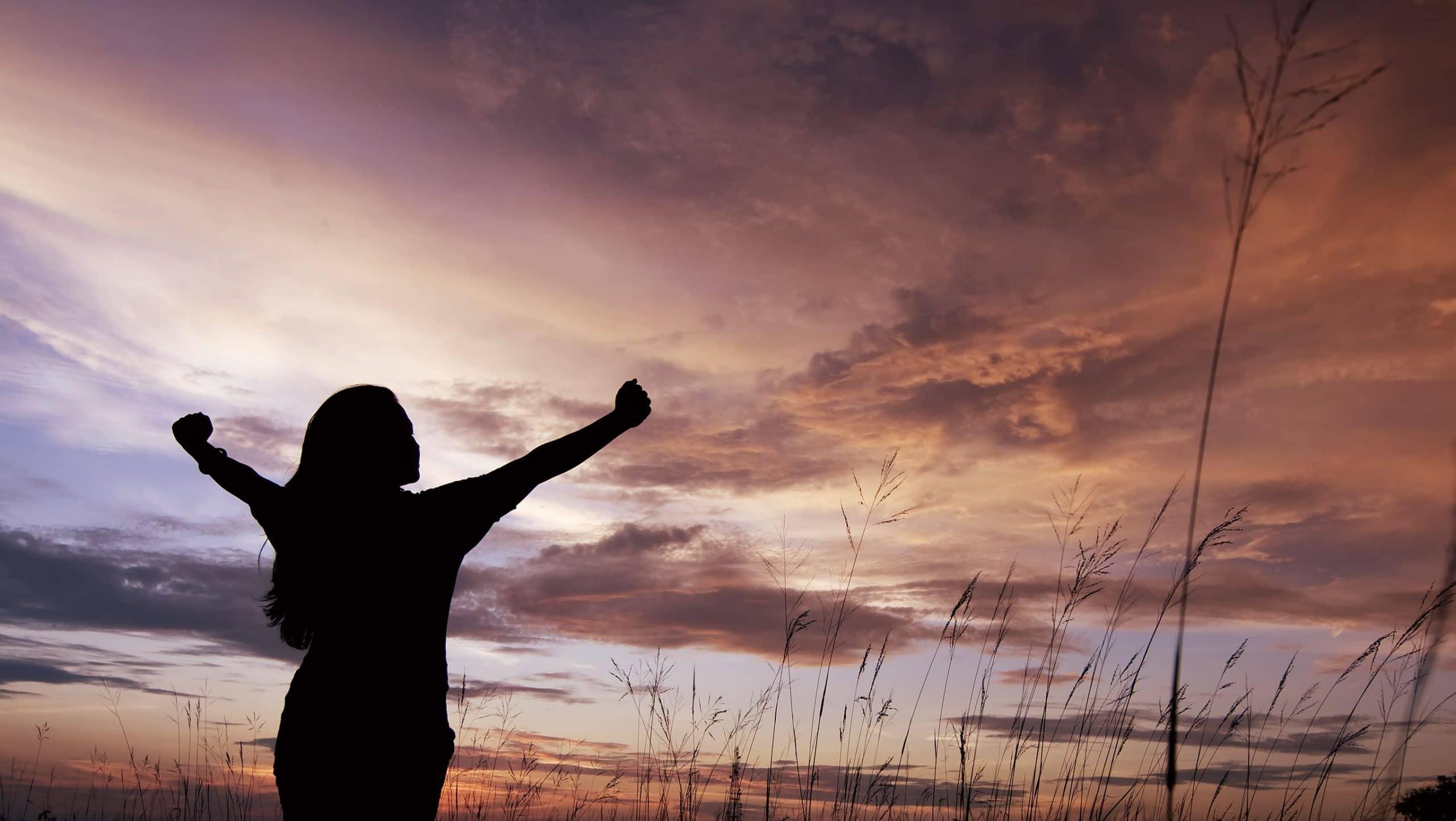 Silhueta de mulher com os braços levantados, olhando pra cima, com o sol se pondo no céu.
