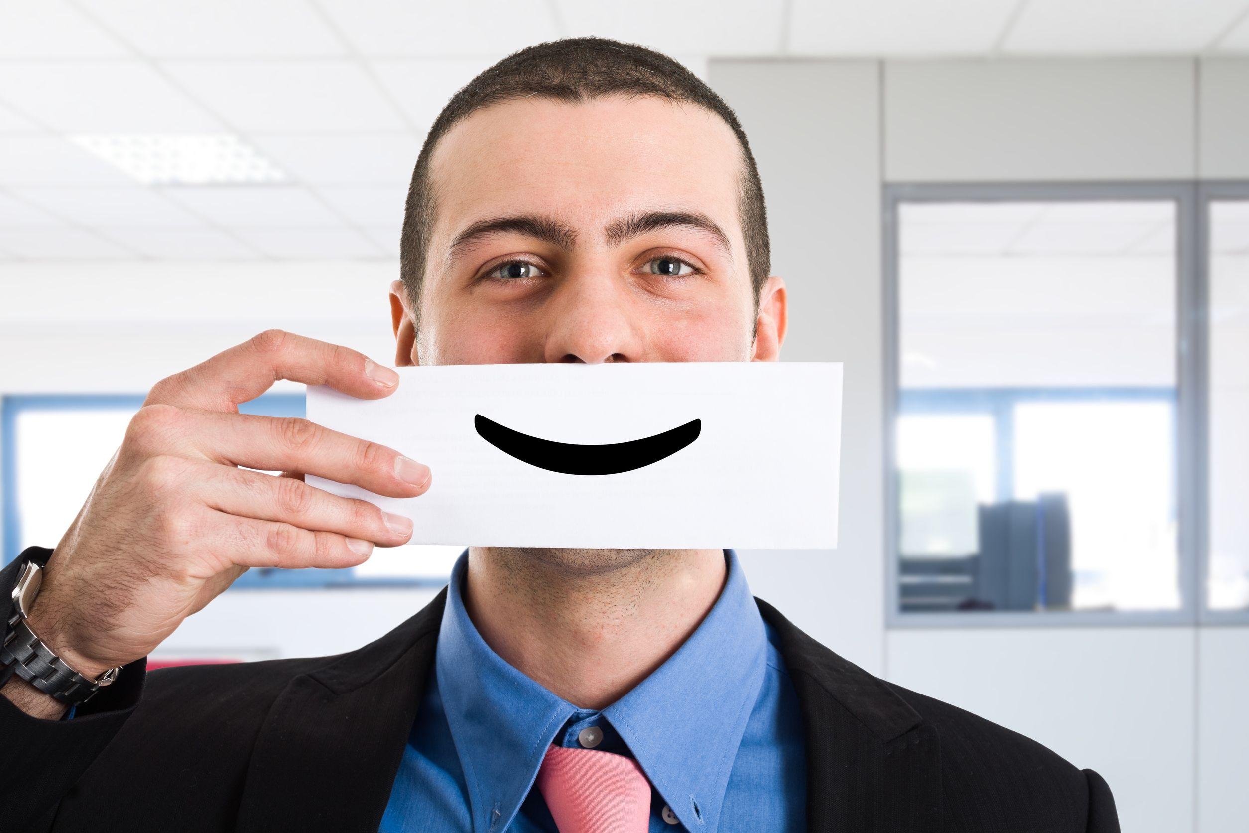 Homem segurando papel com sorriso desenhado em frente a boca