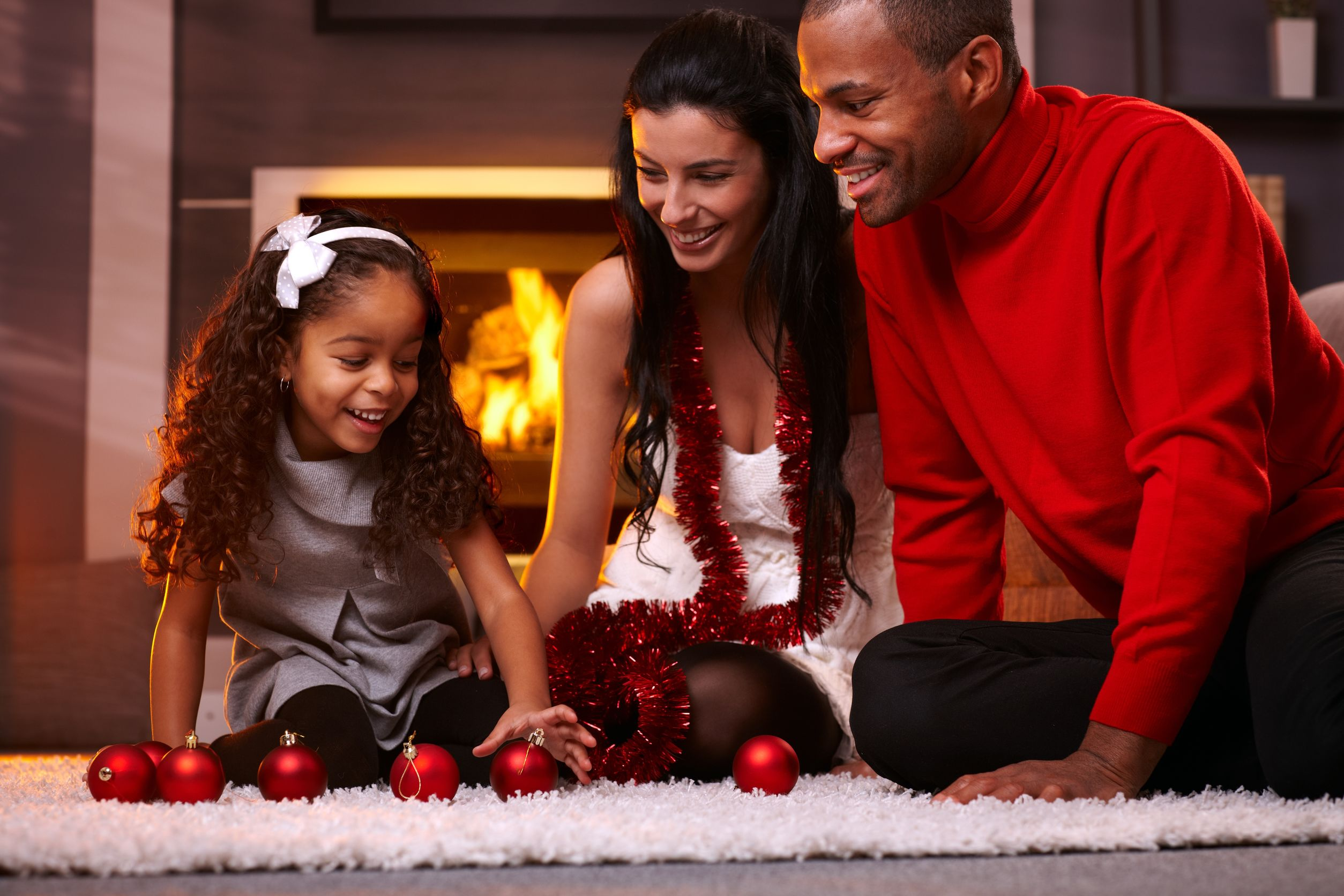 Casal formado por homem negro e mulher branca, sentados no chão com sua filha negra, em cima de uma tapete em frete uma lareira, brincando com enfeites vermelhos de árvore de natal