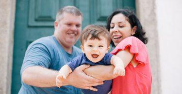 Família composta por mãe, pai e filho. Os pais seguram o filho como se estivesse voando. A mãe é morena e usa uma blusa vermelha. O pai é grisalho e usa uma blusa azul. O filho é moreno e tem o cabelo de tigela e também usa uma blusa azul.