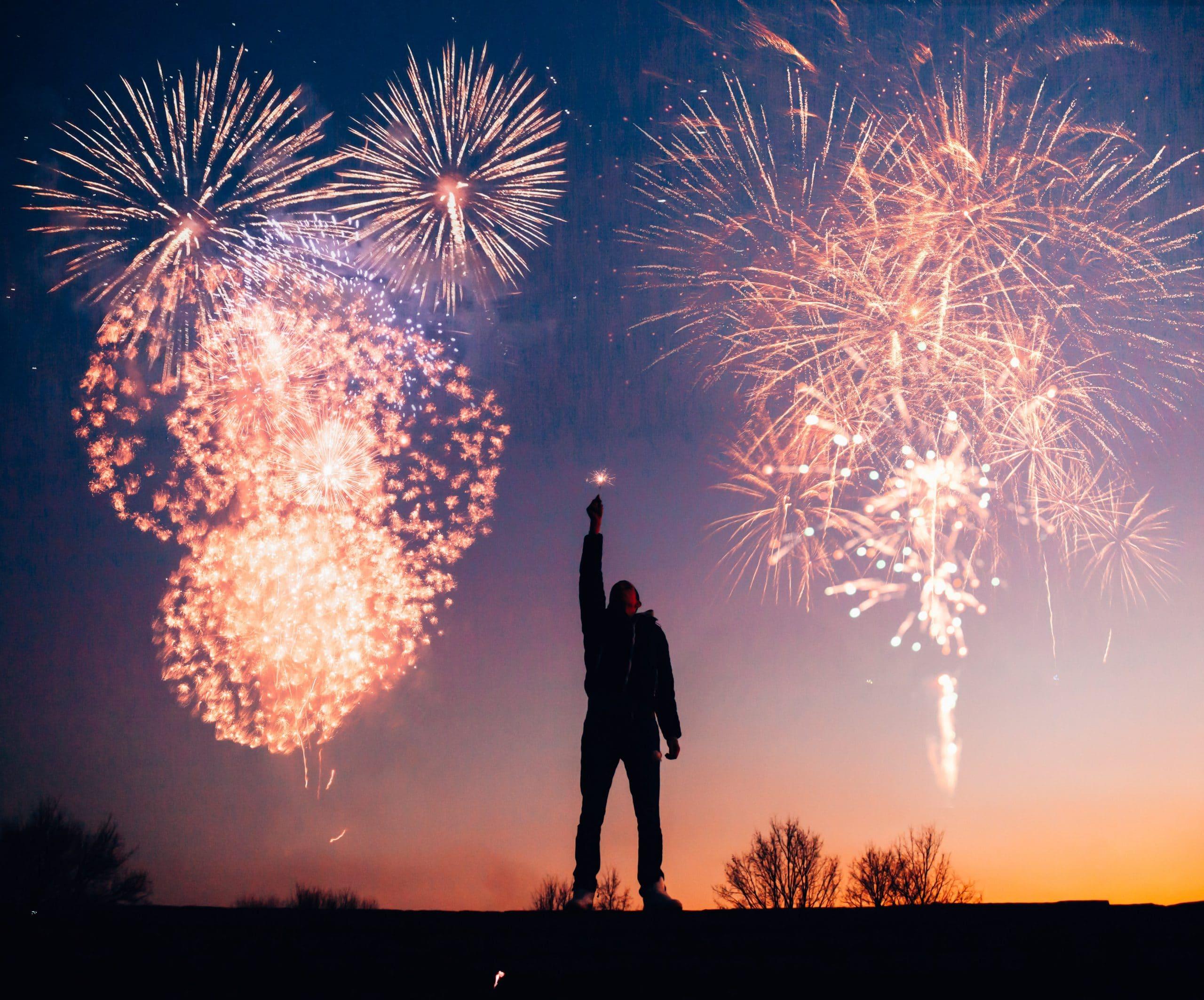 Homem no meio de duas explosões de fogos de artifícios. Ele está com o braço levantado.