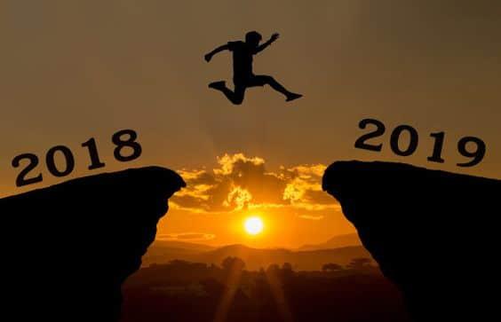 Homem pulando de uma montanha para outra. Fundo de pôr do sol. Em uma montanha escrito 2018 e na outra 2019.