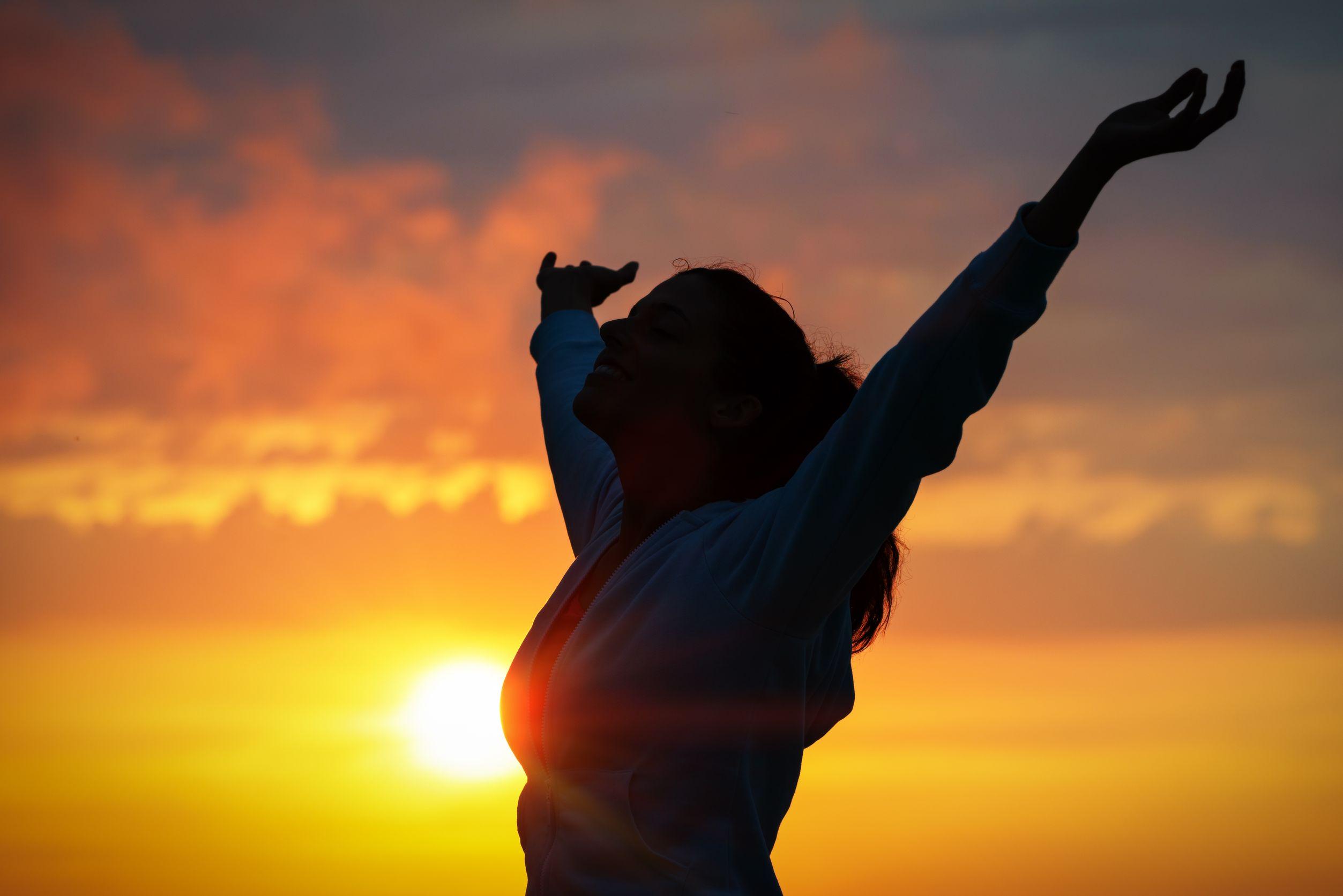 Mulher livre, levantando os braços ao pôr do sol dourado.
