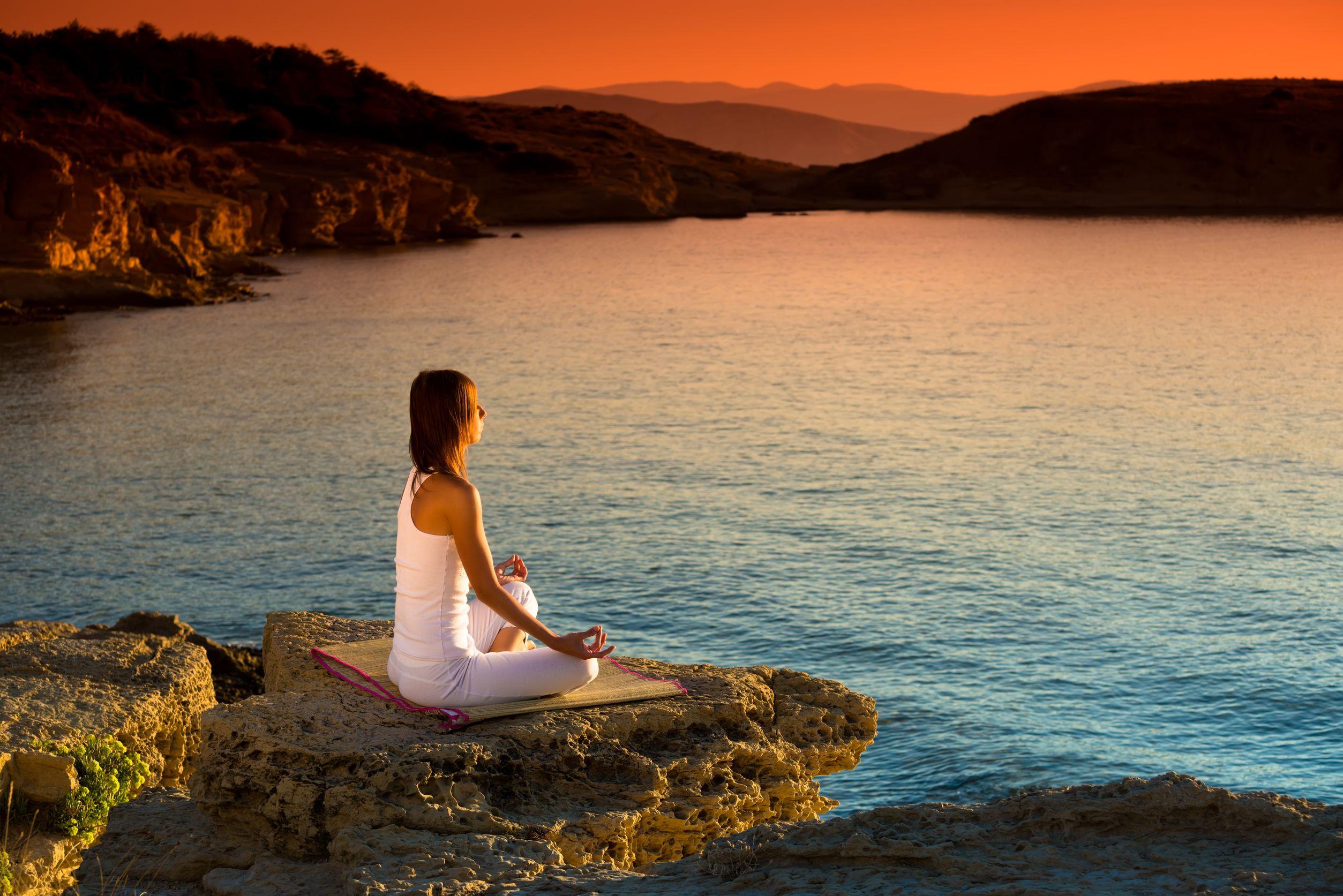 Mulher vestida de branco, sentada em uma pedra de frente para o mar, meditando.