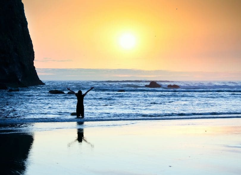 Silhueta de menina em pé nas ondas da praia com os braços levantados ao pôr do sol.