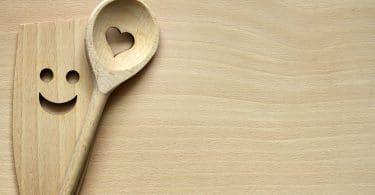 Duas colhes de pau de cozinha, uma com um coração e uma com um rosto sorridente entalhadas, ambas em cima de uma mesa de madeira.