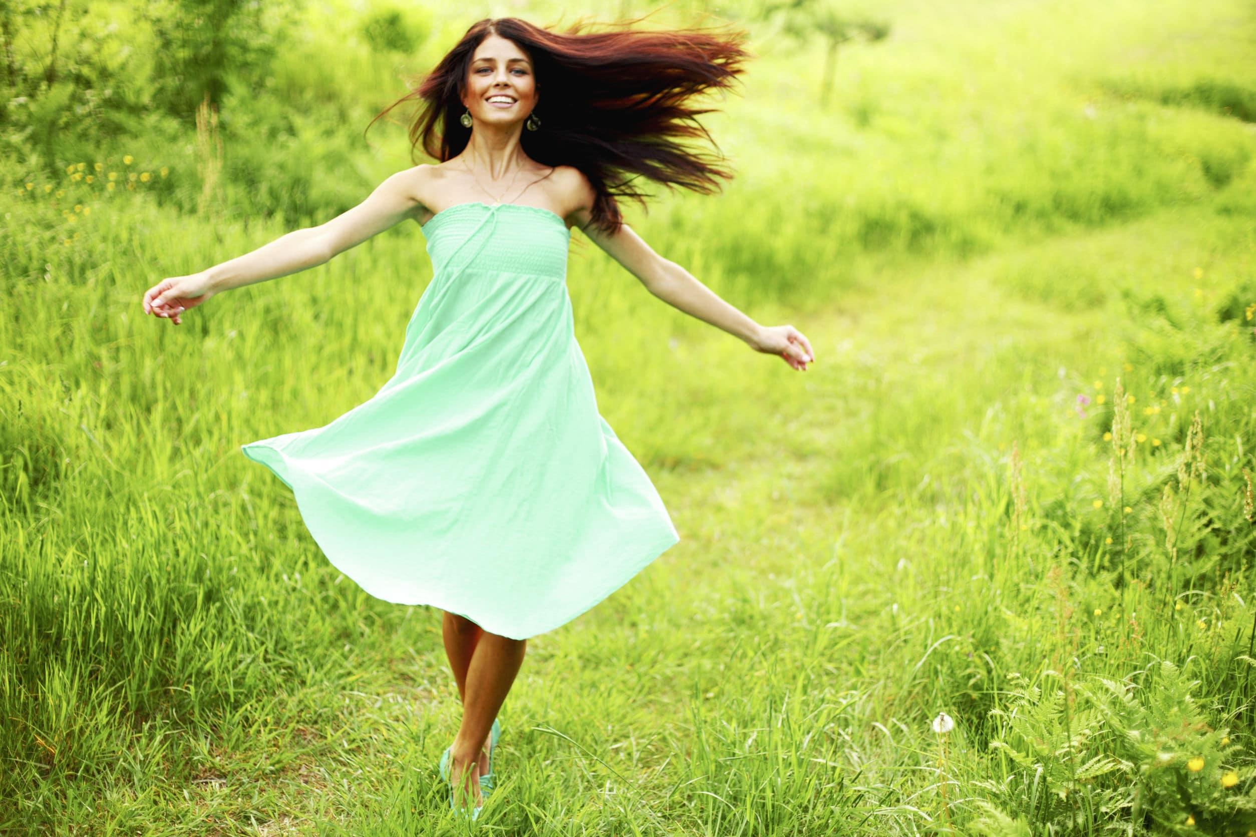 Mulher branca, de cabelos ruivos, com um vestido verde claro, correndo sorridente em um campo verde.