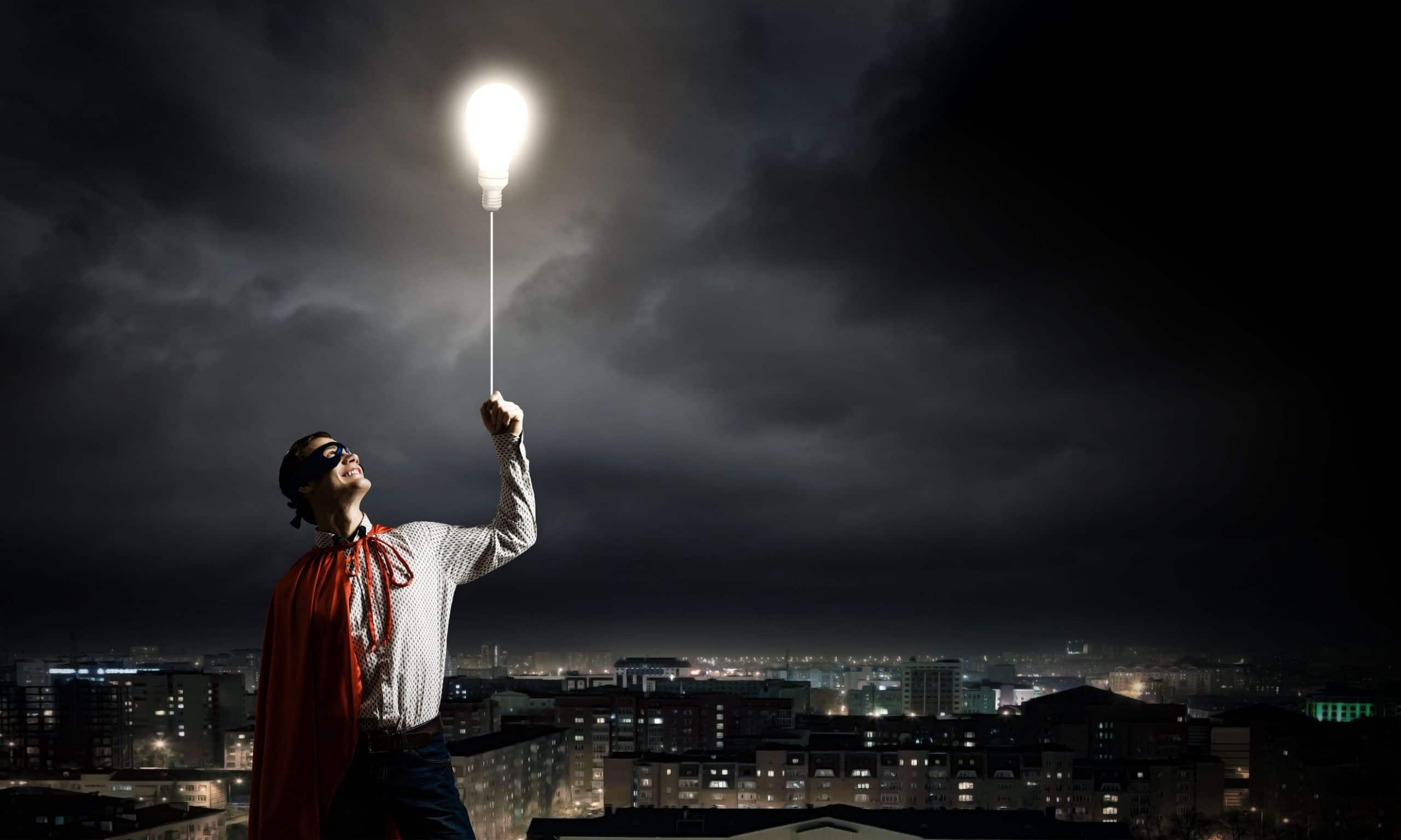 Homem jovem, vestido de super herói, segurando uma lâmpada acesa como um balão, no meio de uma cidade com o céu da noite.