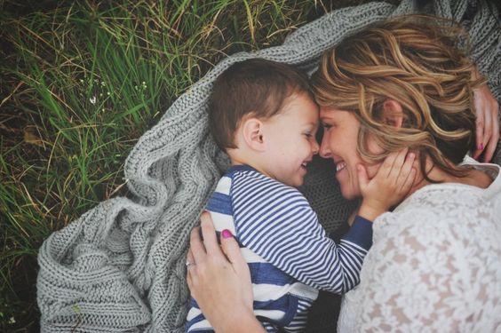 Mãe e filho deitados em gramado. Ela é loira e usa uma blusa branca. Ele é moreno e usa uma blusa azul.