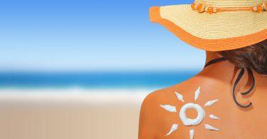 Mulher na praia usando chapéu de palha de costas para a foto. Em suas costas há um desenho feito com protetor solar em formato de sol.