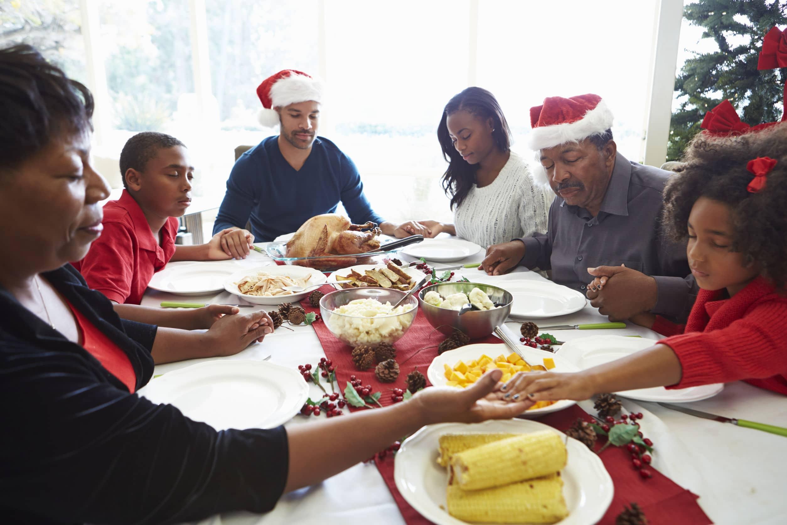 Várias gerações de uma família sentados à mesa orando antes de comer a ceia do Natal.