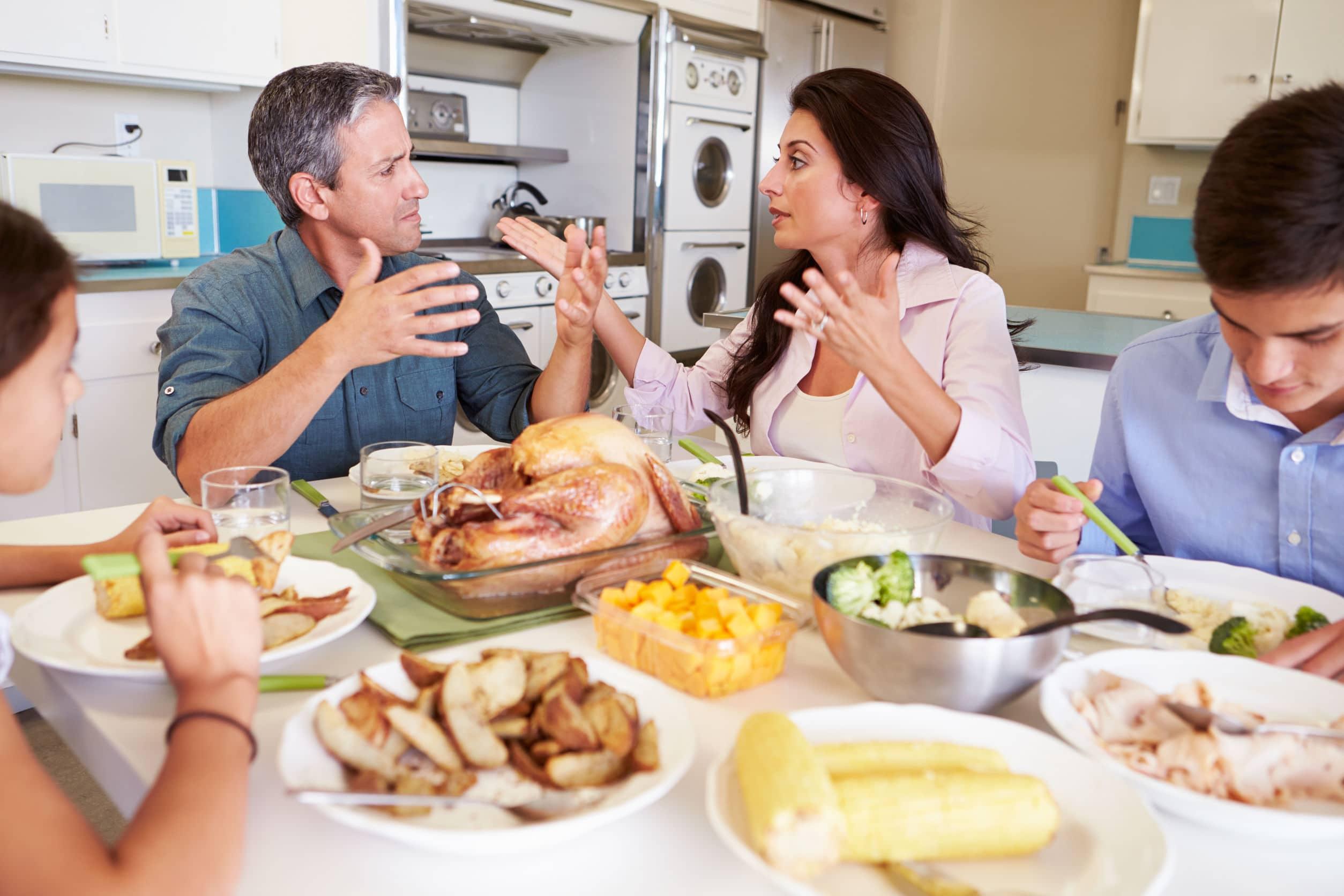 Família discutindo sentados à mesa enquanto jantam.