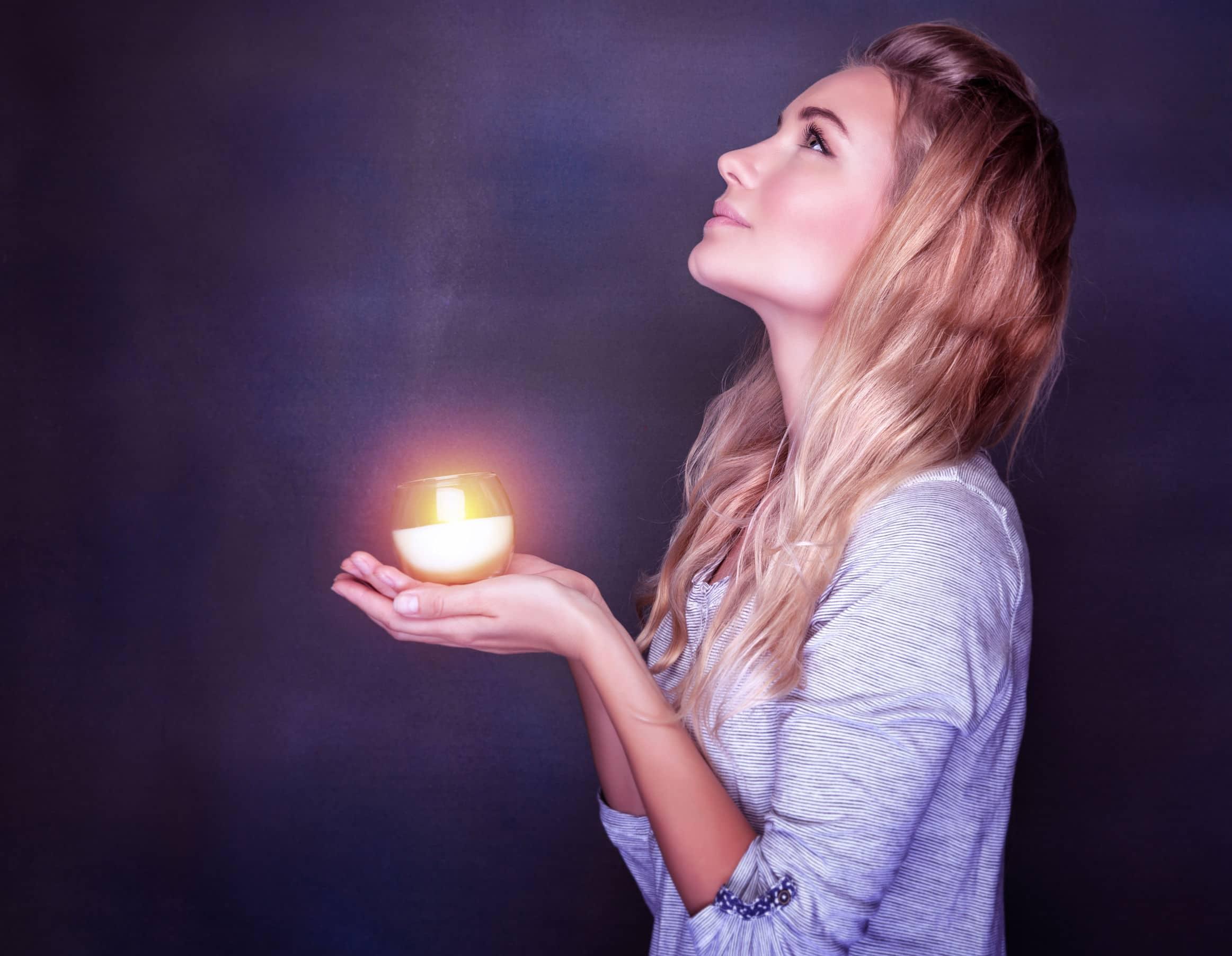Mulher segurando com as duas mãos uma vela acesa, olhando para cima, na frente de um fundo roxo.