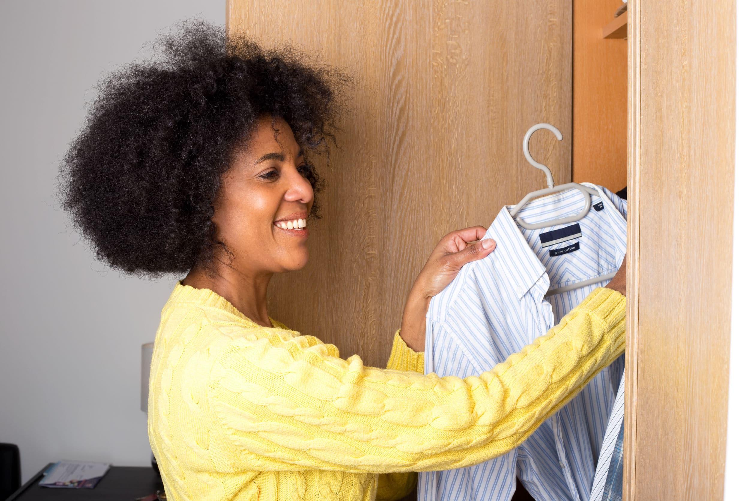jovem mulher negra tirando uma camisa de um guarda-roupa.