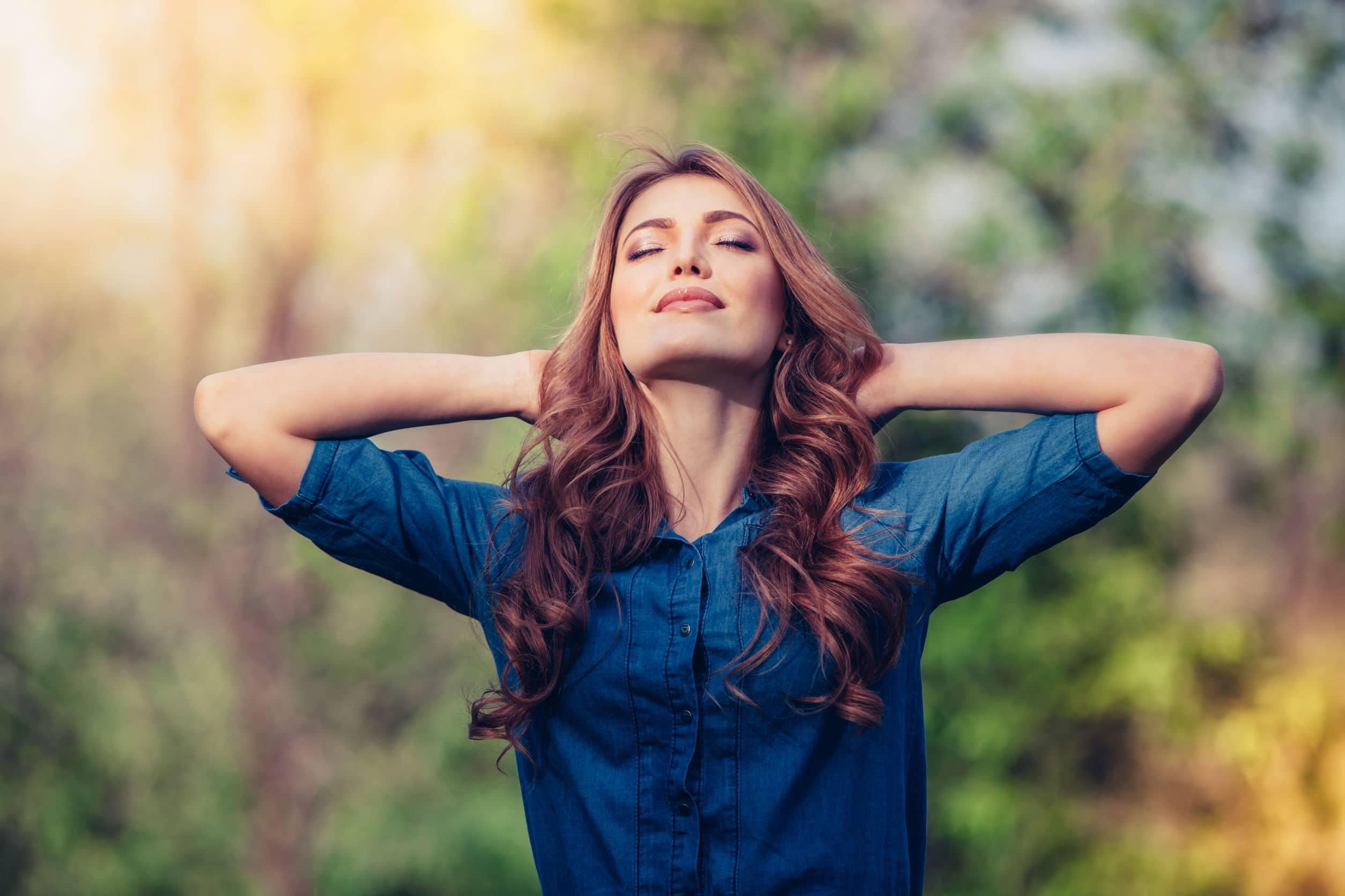 Mulher branca sorrindo de olhos fechados e cabeça levantada e apoiada nos dois braços, em um bosque com o céu ensolarado.