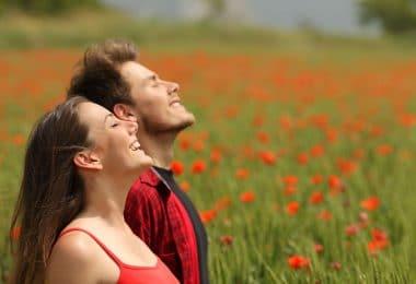 Casal respirando ar puro em um campo cheio de rosas vermelhas.