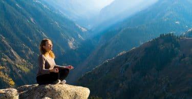 Mulher meditando no alto de uma montanha. Ao fundo uma paisagem de céu azul e montanhas.