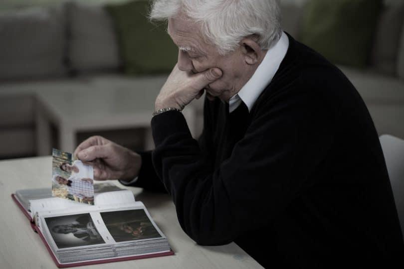 Idoso olhando fotos com a mulher falecida. Provavelmente sofrendo luto.