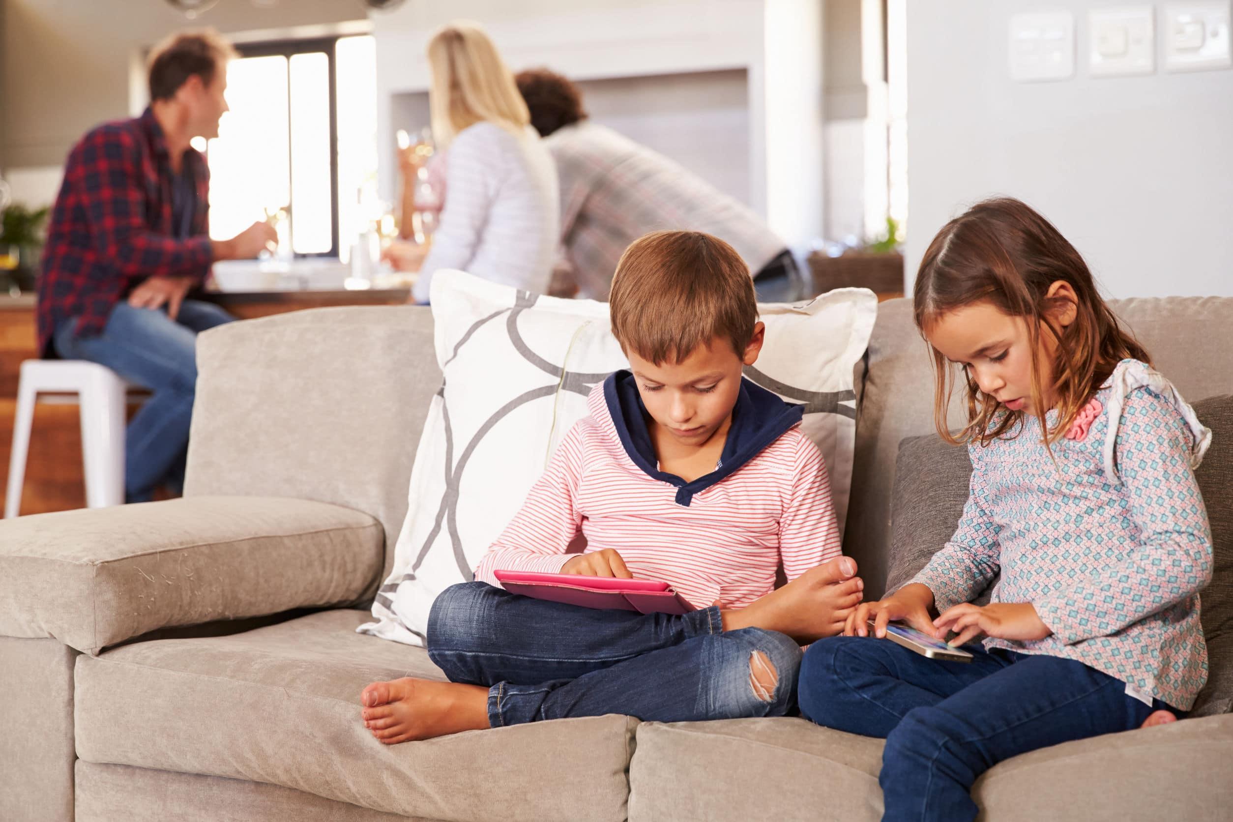 Crianças brincando com aparelhos tecnológicos enquanto os adultos conversam separadamente.