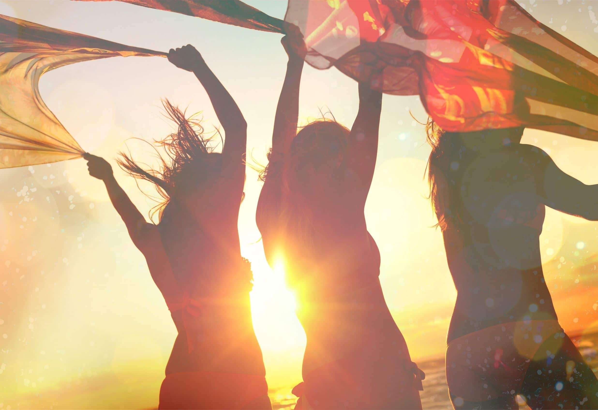 Silhueta de três mulheres pulando, com os braços levantados, segurando panos e correndo em direção o sol.