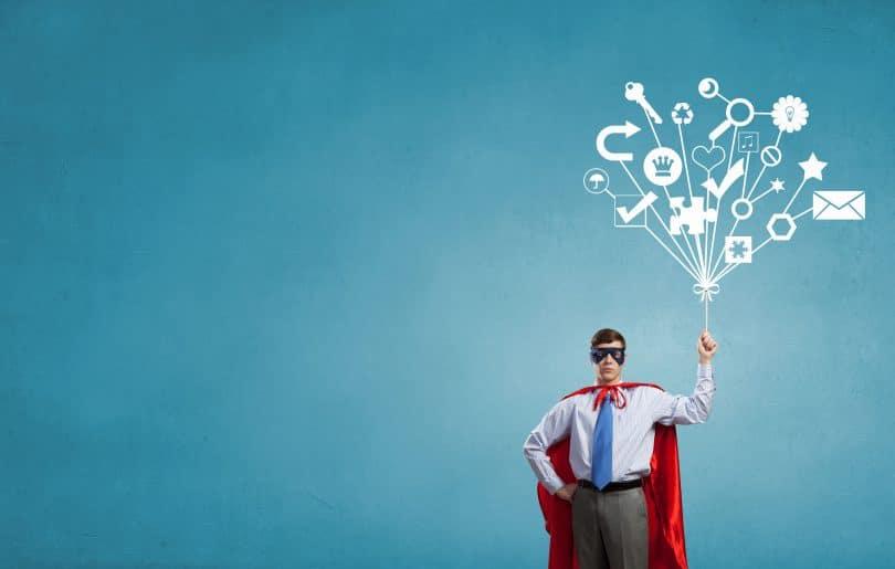 Jovem em traje de super-heróis,, segurando vários desenhos como se fossem balões.