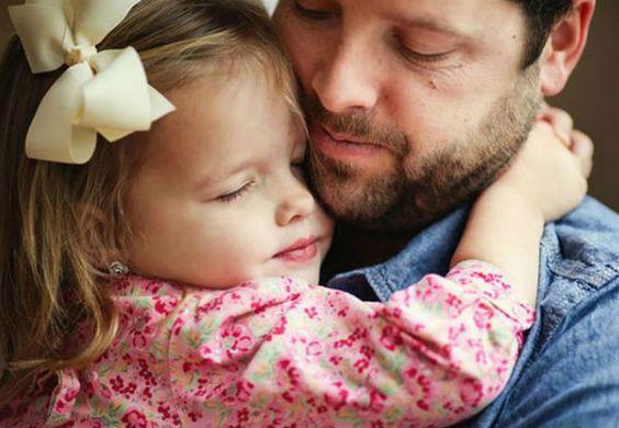 Pai e filha se abraçando. Ela é loira e usa um vestido florido além de um laço branco na cabeça. Ele é moreno e tem barba e usa uma camisa azul.